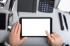 Businessperson Holding Digital Tablet. Close-up Of A Businessperson Holding Blank Screen Digital Tablet On Office Desk Royalty Free Stock Image