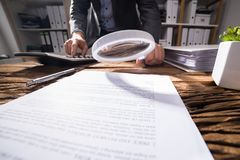 Businessperson Looking At Document With Magnifying Glass stock images
