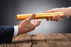 Close-up Of A Businessperson Passing Baton. Close-up Of A Businessperson`s Hand Passing Baton On Wooden Desk stock images