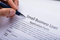 Businessperson Filling Small Business Loan Application Form. Close-up Of A Businessperson`s Hand Filling Small Business Loan Application Form stock photos