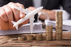 Businessperson Flying Aeroplane Over Stacked Coins. Close-up Of A Businessperson`s Hand Flying Aeroplane Over Stacked Coins At Workplace stock image
