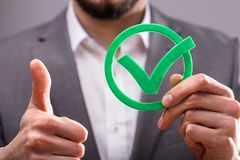 Businessperson Holding Check Mark Icon. Close-up Of A Businessperson`s Hand Holding Green Check Mark Icon stock images