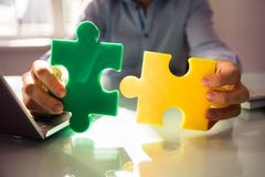 Businessperson`s Hand Holding Two Jigsaw Puzzle stock photos