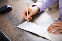 Businessperson`s Hand Signing Cheque stock photo