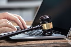Businessperson`s Hand Using Laptop On Wooden Desk. Close-up Of A Businessperson`s Hand Using Laptop With Gavel On Wooden Desk royalty free stock photos