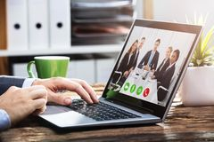 Businessperson Video Conferencing With Colleagues On Laptop stock photos