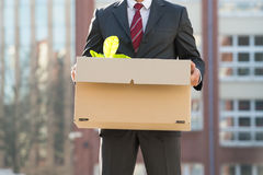 Close-up Of Businessperson Standing With Cardboard Box Outside O Stock Photos