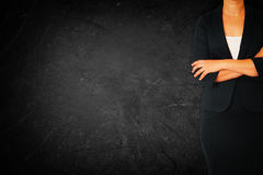 Close up of businesswoman with arms crossed against dark textured background Royalty Free Stock Image