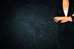 Close up of businesswoman with arms crossed against dark textured background. Stock Photos