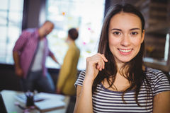 Close-up of businesswoman with coworkers in background Royalty Free Stock Photography