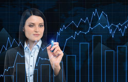 Close up of businesswoman drawing graphs against a world map Stock Photos