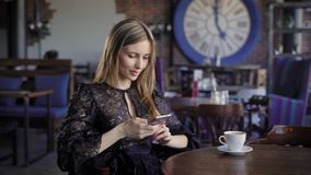 Close up of businesswoman dressed in black dress is sitting in cafe using modern smartphone. Adorable lady is relaxing. At the table during the lunch typing stock footage