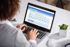 Businesswoman Filling Online Survey Form. Close-up Of A Businesswoman Filling Survey On Laptop At Workplace royalty free stock images