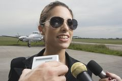 Close-up of a businesswoman giving interview at an airport Stock Image