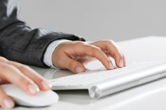 Closeup of businesswoman hand typing on keyboard with mouse on wood table royalty free stock images