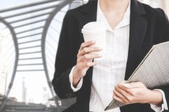 Close up of businesswoman holding a coffee cup. And document report walking in the cityscape haste time. Business and Lifestyle Concept Royalty Free Stock Image