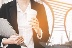 Close up of businesswoman holding a coffee cup and document report walking in the cityscape haste time. royalty free stock photo