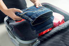 Close up of businesswoman packing clothes into travel bag. Luggage and people concept Stock Images