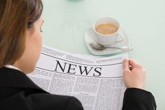 Close-up Of Businesswoman Reading Newspaper. With Cup Of Coffee On Desk Stock Photos