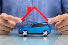 Businesswoman Protecting Car With Red Roof. Close-up Of A Businesswoman`s Hand Protecting Blue Car With Red Roof royalty free stock photo