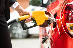 Close-up Of Businesswoman`s Hand Refueling Car`s Tank royalty free stock images