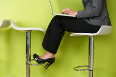 Close Up Of Businesswoman Sitting On Stool Using Laptop Royalty Free Stock Photos