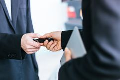 Businesswoman taking a car key from a salesman. Close up businesswoman is taking a car key from a car salesman Royalty Free Stock Photography