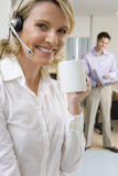 Close-up of businesswoman wearing headset holding mug, man in background, smiling, portrait Stock Images