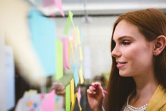 Close-up of businesswoman writing on sticky notes Stock Photo