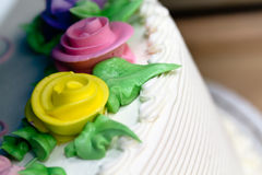 Close Up of Buttercream Roses on a Birthday Cake. Yellow and pink buttercream frosting roses with green leaves and white icing stock images