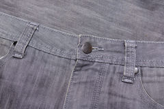 Close up of button on grey jeans Stock Images