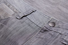 Close up of button on washed grey jeans Stock Photo