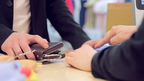 Close-up buyer`s hands in payment by card using the payment terminal in store. Young adults couple in good mood shopping at the clothing store. Lifestyle concept stock footage