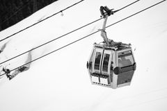 Close up on cable cabin gondola taking people to the top of snowy mountain to ski slopes. In black and white royalty free stock images