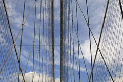 Close Up Of Cables on Brooklyn Bridge. A mirror like image of two horizontal lines of cables, with a pretty blue sky with wispy clouds in the background Royalty Free Stock Images