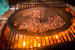 Close up of cacao bean inside of a metallic tray, over a wood stove, roasting cocoa beans Royalty Free Stock Photo