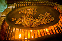 Close up of cacao bean inside of a metallic tray, over a wood stove, roasting cocoa beans Stock Images