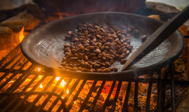 Close up of cacao bean inside of a metallic tray, over a wood stove, roasting cocoa beans.  Royalty Free Stock Photos