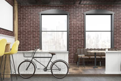 Close up of a cafe interior with brick walls and a bicycle Royalty Free Stock Images