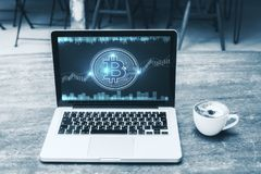 Economy and e-commerce concept. Close up of cafe table with digital bitcoin on laptop screen and coffee cup. Economy and e-commerce concept stock photography