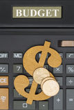 Close-up of a calculator with a dollar sign and gold coins Stock Photos