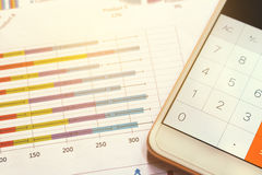 Close up calculator in smartphone and summary report on table office.  Royalty Free Stock Images