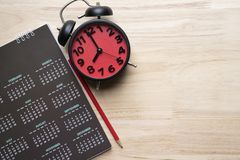 Close up of calendar, alarm clock and pencil on the table Royalty Free Stock Image