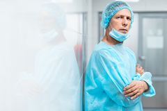 Close up of calm doctor standing near the wall and frowning royalty free stock photography