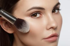 Serious young woman putting on powder on face. Close up of calm female face. Pretty girl is applying blush on cheek by brush Royalty Free Stock Photo