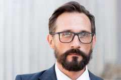 Close up of calm man wearing glasses and looking at you royalty free stock photography