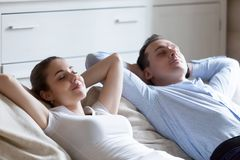 Man and woman lying on sofa relaxing with eyes closed. Close up of calm men and women lying on cozy couch hands over head relaxing after working day, peaceful royalty free stock photography