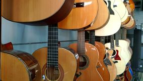 Close-up camera along acoustic and electric guitars in the store of musical instruments. Close-up camera along acoustic and electric guitars in the store of