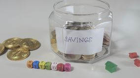 Savings of money for buying property for bitcoins. Close-up. Camera moves from left to right. Glass jar with savings with coins stands at the back of cubes with stock footage