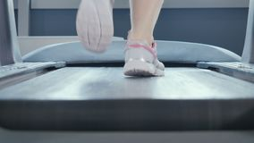 Woman runs on the treadmill. Close-up. The camera moves from the left to right. Young woman wearing sporty sneakers is in the gym. Sporty young woman is at the stock footage